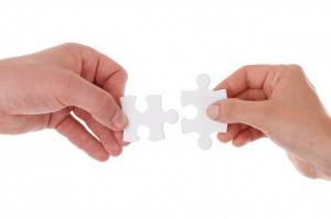 two hands putting together puzzle pieces